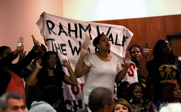 Demonstrators from Walk the Walk interrupt a City Council meeting to shout slogans concerning upcoming school closings. The group was ushered out of the chambers.