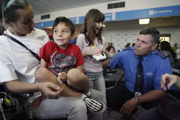 "Clinical supervisor Taeja Klug, from far left, gets Jacob Sanchez, 7, to respond to JetBlue chief pilot James Daulton, far right, during Jet Blue, Pacific Child and Family and TSA's ""Wings for Autism"" program, which took place at Bob Hope Airport in Burbank on Saturday, May 4, 2013. ""When you have events for kids with autism like this, it brings the anxiety down,"" Jennifer Slater-Sanchez said. Jennifer is the mother of Jacob who was diagnosed with autism as a three-year-old."