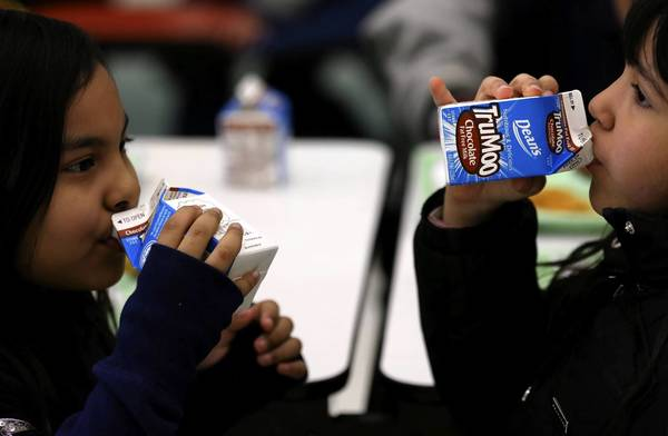 Children drink milk during lunchtime at Sharon Christa McAuliffe Elementary School in Chicago on Friday. Three of the largest districts in Illinois — Chicago Public Schools, Naperville and Elgin-based U-46 — say they do not offer artificially sweetened milk.