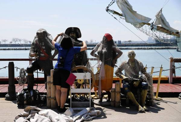 A worker a Navy Pier covers a set of pirate statues, as a tall ship arrives to take media members for a free ride, after a news conference about this year's Tall Ships event.