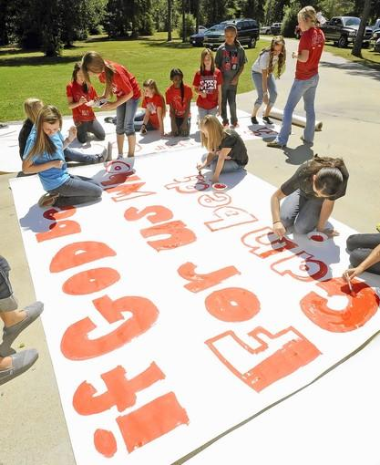 Cheerleaders and other children work on a banner in Kountze, Texas.