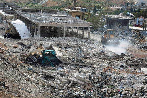 Workers clear the rubble of buildings destroyed by an Israeli airstrike in Damascus, Syria.