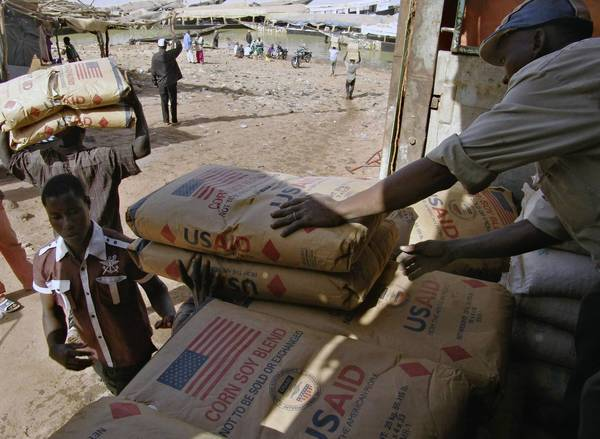Men place humanitarian food aid on to flat-bottom boats in Mopti, Mali. The Obama administration plans to reform the Food for Peace Program by focusing more aid on food produced in the countries where it's consumed.