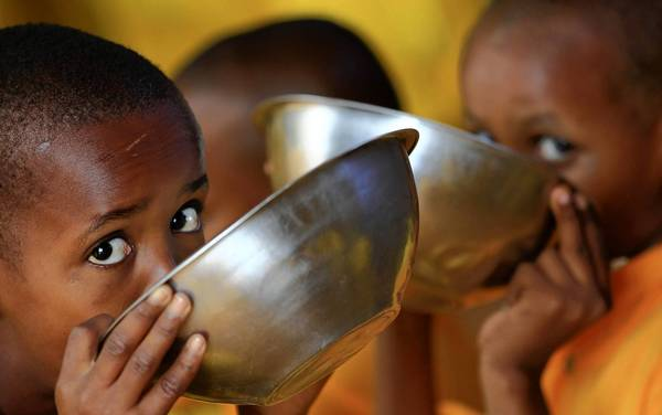 Somali refugee children eat porridge at the Ifo refugee camp in Dadaab, near the Kenya-Somalia border.