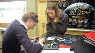 Josie McKenzie and Emily Cook begin assembly of a fuel cell.