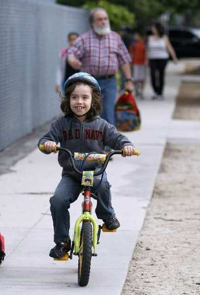 R.D. White Elementary School 1st grader Rafael Bodeant, 7, arrives to school on his bike, with his father Rafael Bodeant behind him, on Bike to School Day at the Glendale school on Wednesday, May 8, 2013. About 25 children rode their bikes to school from various locations.