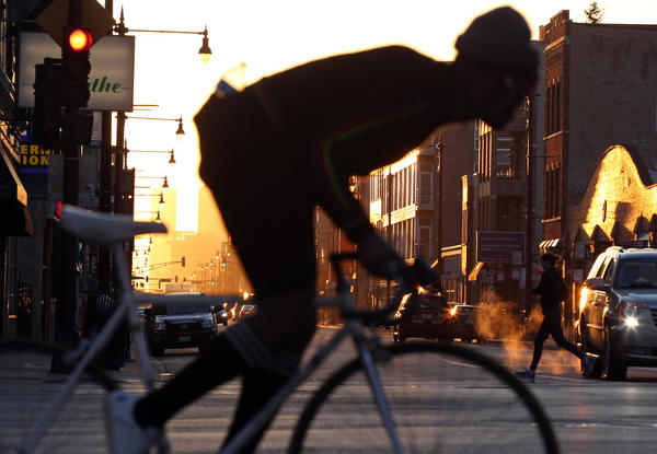 A bicyclist and jogger cross North Avenue at Milwaukee Avenue as the sun rises on a late March morning.