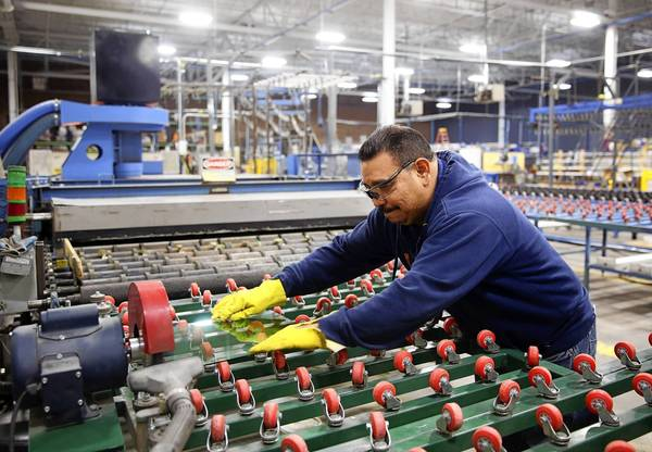 Joel Cruz works on the glass line Friday at the New Era Windows Cooperative in Chicago. The cooperative comprises former employees of Republic Windows & Doors.