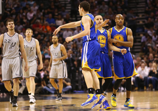 Klay Thompson celebrates a three-point shot with Stephen Curry and Jarrett Jack against the Spurs.