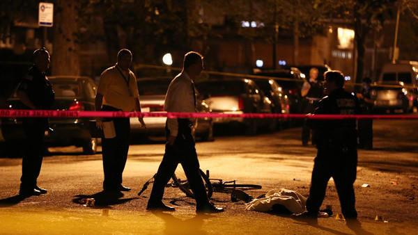 Police investigate the scene after a man was shot and killed while riding his bicycle Wednesday, May 8, 2013 near the intersection of West 102nd Street and South Green Street in Chicago.
