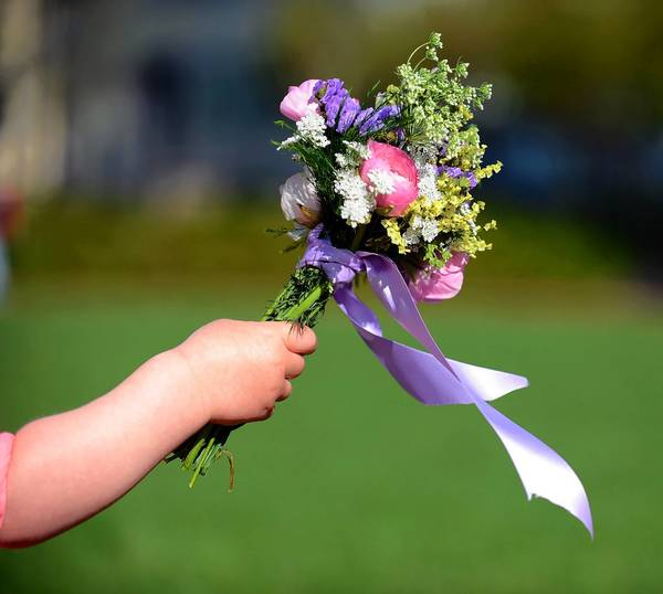 Laura Kackenmeister, 2, reaches out to mom with a bouquetfor Mother's Day.
