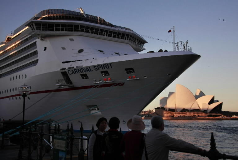 """Onlookers stand below a Carnival Cruise Lines ship called the """"Carnival Spirit"""" as it sits docked opposite the Sydney Opera House May 9, 2013. Local media reported that an air and marine search is underway along a large stretch of the New South Wales coast for two people who went missing from the cruise ship last night, adding that a spokesman for Carnival Cruise Lines has said that two people could not be accounted for during the disembarkation process this morning. REUTERS/David Gray"""