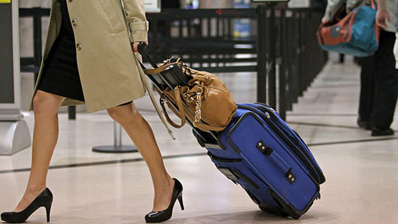 A passenger carries her rolling luggage near the security checkpoint at Hartsfield-Jackson Atlanta International Airport in April.