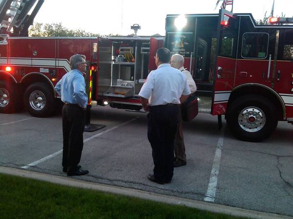 Village Trustee Brian Maher, Assistant Fire Chief Stephen Klotz and Public Works Director Dale Schepers huddle around Tinley Park's new fire truck.