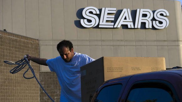 A customer secures a washing machine to his truck outside a Sears store in Richmond, Va.