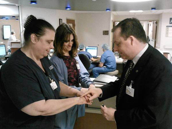 Mark Woolfington, chaplain at Adventist La Grange hospital, blesses the hands of secretary Pam Brown, left, and nurse Amy Kosowski.