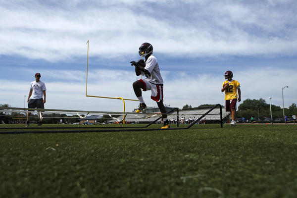 Loyola Academy running backs run warm-up drills in Wilmette during a preseason practice in August.