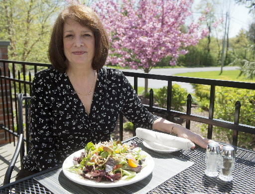 Manager Marcia Short poses on the restaurant patio with an Asian Salad at the Brick Tavern in Quakertown on Wednesday.