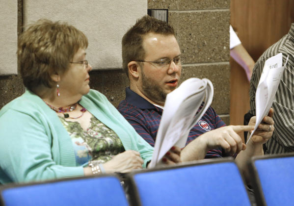 Brandon Christiansen, right, points out some information in the Buxton Co. report to fellow Lakewood Mall employee Karla Spear before Thursday's presentation of a study of the Aberdeen retail marketplace.