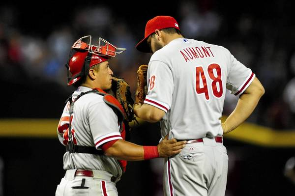 Philadelphia Phillies catcher Carlos Ruiz (51) talks with relief pitcher Phillippe Aumont (48) during the seventh inning at Chase Field.