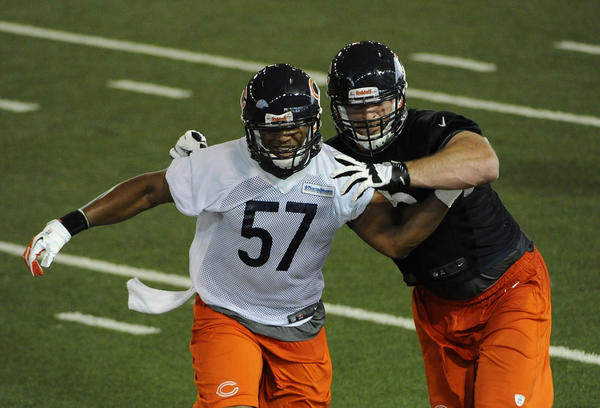 Kyle Long (right) and Jonathan Bostic (left) go through drills during rookie camp Friday.