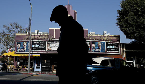 A pedestrian walks past the Los Feliz Theater on Vermont Avenue, a landmark of the Los Feliz neighborhood of Los Angeles.