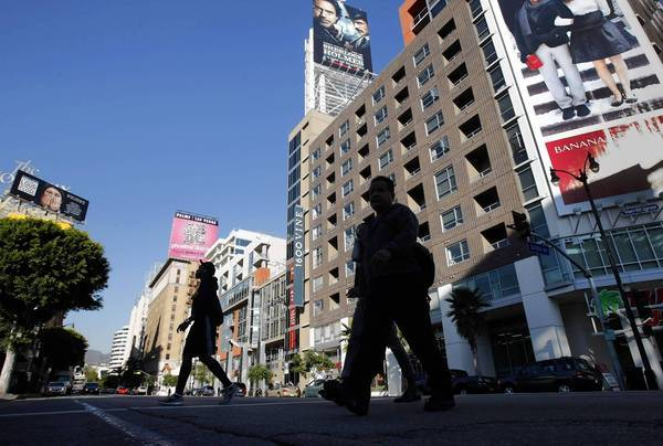 "Pedestrians walk past high–rise buildings along Vine Street in Hollywood. Over 12 years as the area's councilman, mayoral candidate Eric Garcetti has emerged as a leading champion of ""smart growth,"" which aims to entice residents out of their cars by densely concentrating new development along transit lines. Activists worry about rising rents and traffic-choked streets."