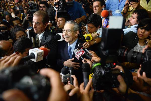 Former Guatemalan dictator Efrain Rios Montt, 86, is surrounded by microphones after being sentenced on genocide charges in Guatemala City.