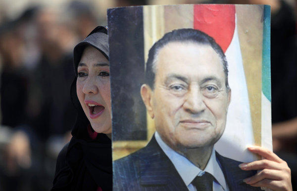 A supporter of Egypt's ousted president, Hosni Mubarak, takes part in a rally outside a courtroom in Cairo.