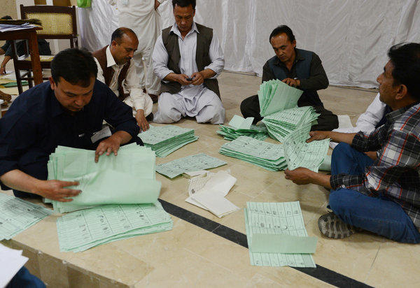 Pakistani election officials count ballot papers.