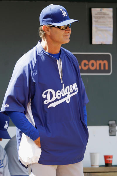 Dodgers manager Don Mattingly looks on from the dugout.