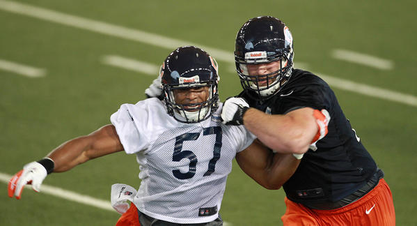 Jonathan Bostic (57) fights off Kyle Long at rookie minicamp.