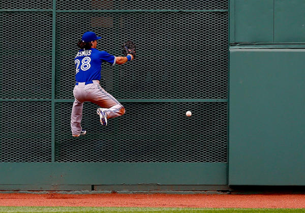 Toronto Blue Jays center fielder Colby Rasmus misses a fly ball in center field before running into the fence.