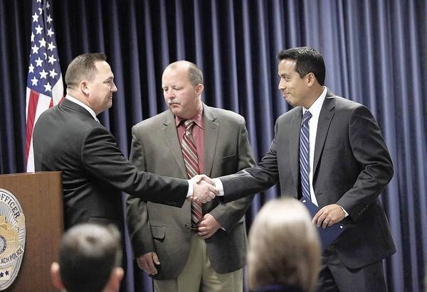 Newport Beach Police Department Capt. Dale Johnson, left, and Det. David Syvock, center, honor Ron Perez, a special agent with the Homeland Security Investigations, during a ceremony to recognize individual contributions to the Orange County Child Task Force in April.