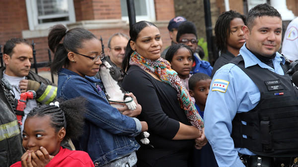 Chicago police officer Edward Leighton, right, describes how he helped rescue Zabrina Washington, second from right, and her six children from a fire Saturday, May 11, 2013 in their Lawndale home on the 1900 Block of South Drake Ave.