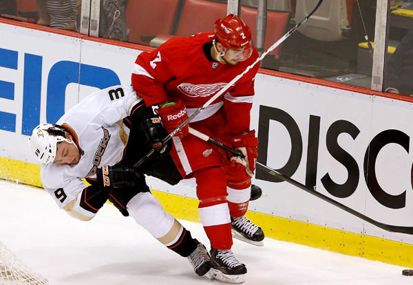 Detroit Red Wings' Brendan Smith controls the puck as Anaheim Ducks' Matt Beleskey falls to the ice.