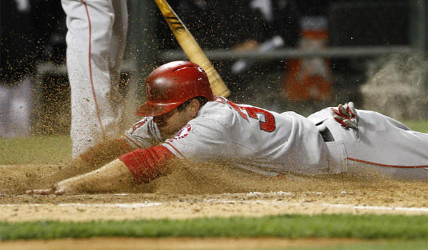 Outfielder J.B. Shuck dives across home plate Friday night while playing in his 10th straight game for the injury-depleted Angels.