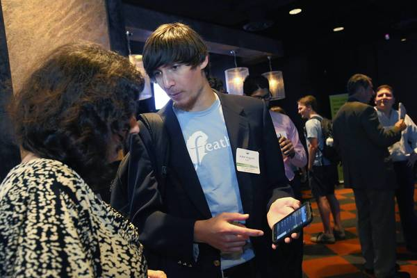 Aidan Augustin shows his Feathr app at VenturePitch Orlando last week. At the event, startups promote their products to investors.