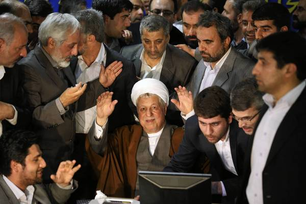 Former Iranian President Ali Akbar Hashemi Rafsanjani, center, waves as he registers at the Interior Ministry in Tehran to pursue a bid to return to office. Rafsanjani, 78, who served as president from 1989 to 1997, has been viewed as a possible voice of reform against the hard-line clerical establishment.