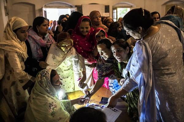 Pakistani women receive ballot papers before casting their votes at a polling station in Lahore. Turnout was high for the country's first democratic transfer of governance.