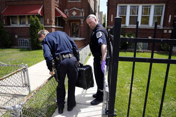 Chicago police forensic officers investigate the scene where an elderly woman was reported to be fatally stabbed on Sunday.