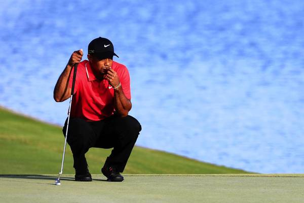 Tiger Woods lines up a putt on the 18th green during the final round of THE PLAYERS Championship at TPC Sawgrass in Ponte Vedra Beach, Fla.