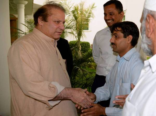 Former Pakistani Prime Minister Nawaz Sharif, left, meets with party supporters in Lahore. With his party's clear margin of victory in elections, he is expected to become prime minister for an unprecedented third time.