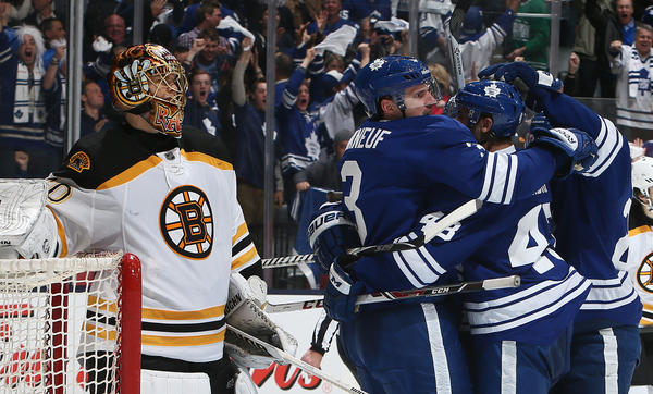 The Maple Leafs celebrate Dion Phaneuf's goal in front of Bruins goalie Tuukka Rask.