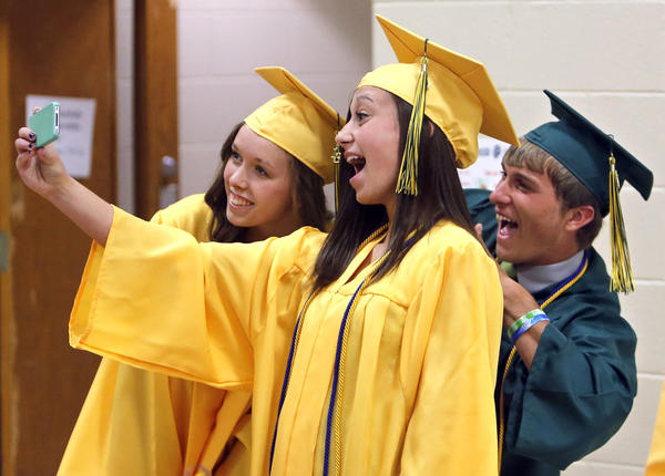 Allison Chamberlain, center, takes a photo of herself and classmate Alyssa Wherry, left, as Kyle Martin, right, jumps in the picture as the trio of Aberdeen Roncalli graduates waited for the 47th annual commencement to begin Sunday afternoon.