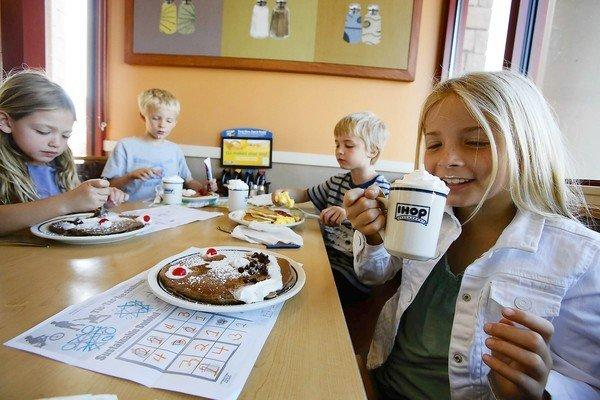 Marley Abowitz, 9, right, with her siblings 7-year-old Brody, Aidan and Ruby, 6, sips on a drink at IHOP restaurant in Los Angeles.