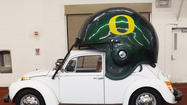 Some lucky Oregon Ducks fan can bid on a 1973 vintage Volkswagen Beetle that features a gigantic life-size helmet on the roof.