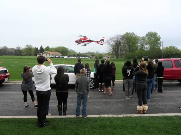 Glenbard South High School students watch as a Superior patient transport helicopter lands on a field at the school.
