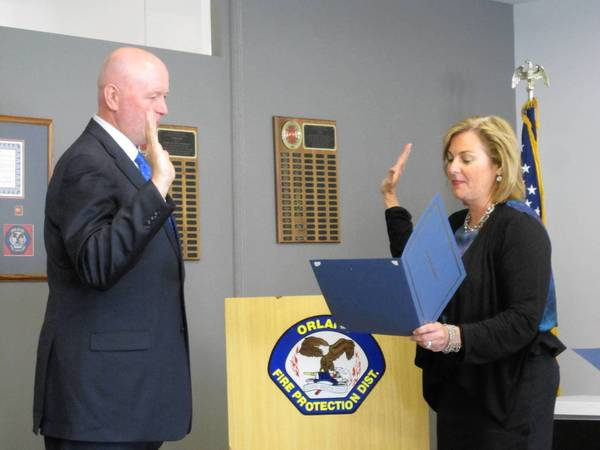 Cook County Commissioner Liz Gorman swears in new Orland Fire Protection District Trustee John Brudnak.