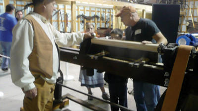 Rich Yoder, Springs Museum Curator, with Ron Paul, Springs, demonstrate lathe operation in the Folk Annex of the Springs Museum.
